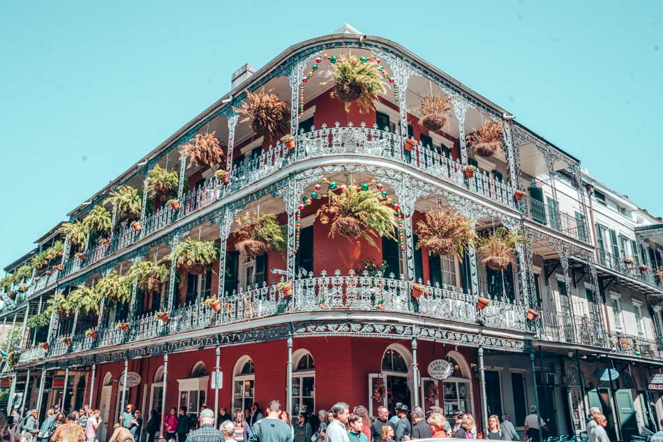 Iconic facade with hanging plants and ironwork lattice fences in the French Quarter, New Orleans, Louisiana.