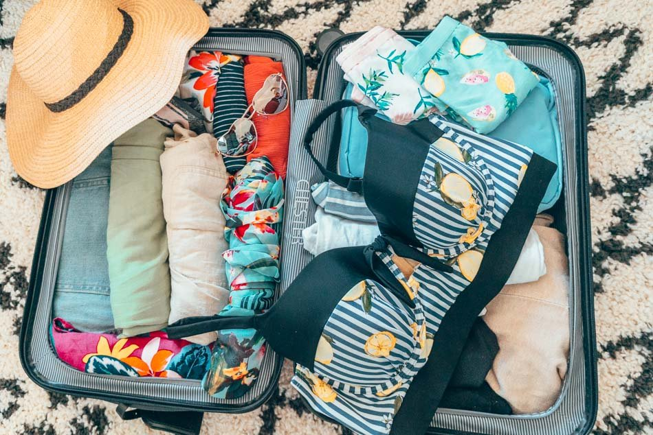 Swimsuit top with lemon print on a packed suitcase.