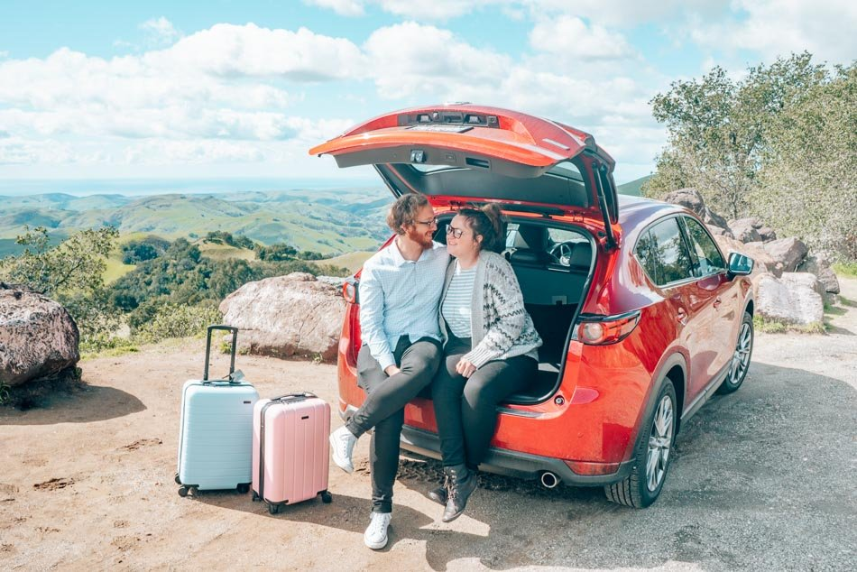 Travel couple and suitcases in the perfect rental car to explore Highway 1 to visit the Central Coast, California.
