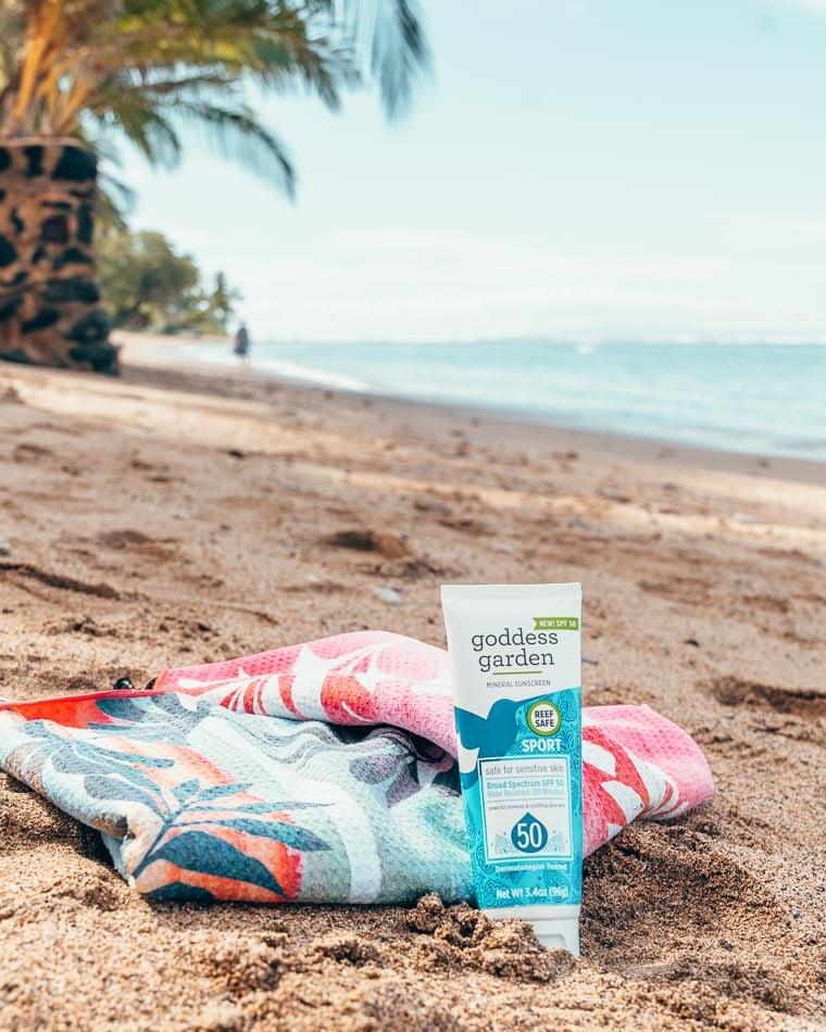 Mineral sunscreen by Goddess Garden on the beach, a reef-safe sunscreen.
