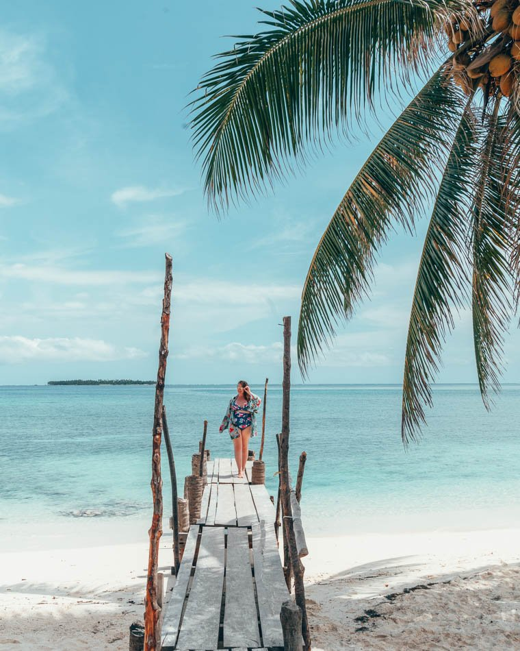 Curvy girl on a dock in front of a bright blue sea with a palm tree in one corner.