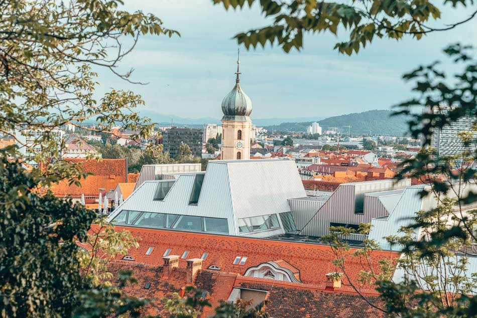A view of Graz from above, through the trees.