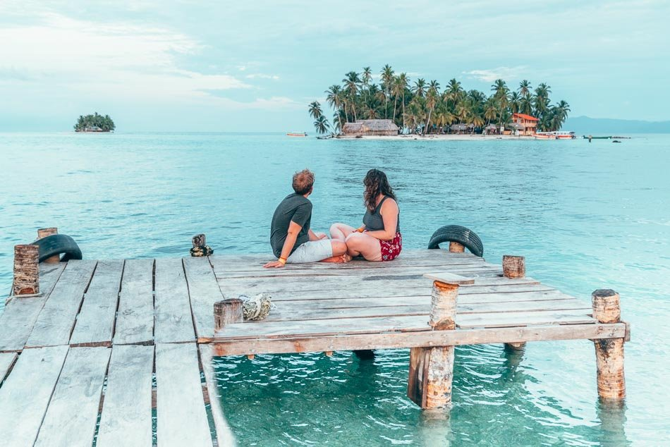 Couple gazing at an island in the Caribbean ocean.