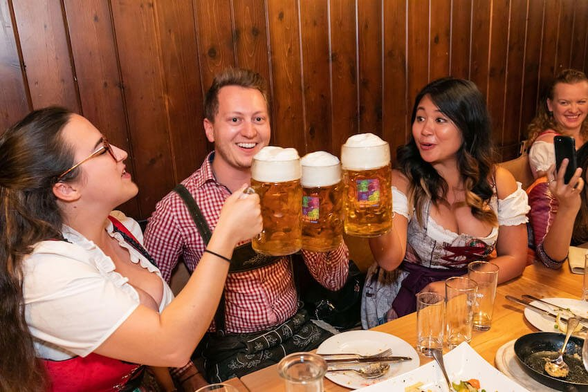 Travel bloggers drinking giant beers in traditional outfits in Graz, Austria.