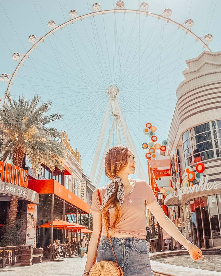 Girl standing at the LINQ Hotel and casino strip in front of the High Roller ferris wheel in Las Vegas, Nevada.