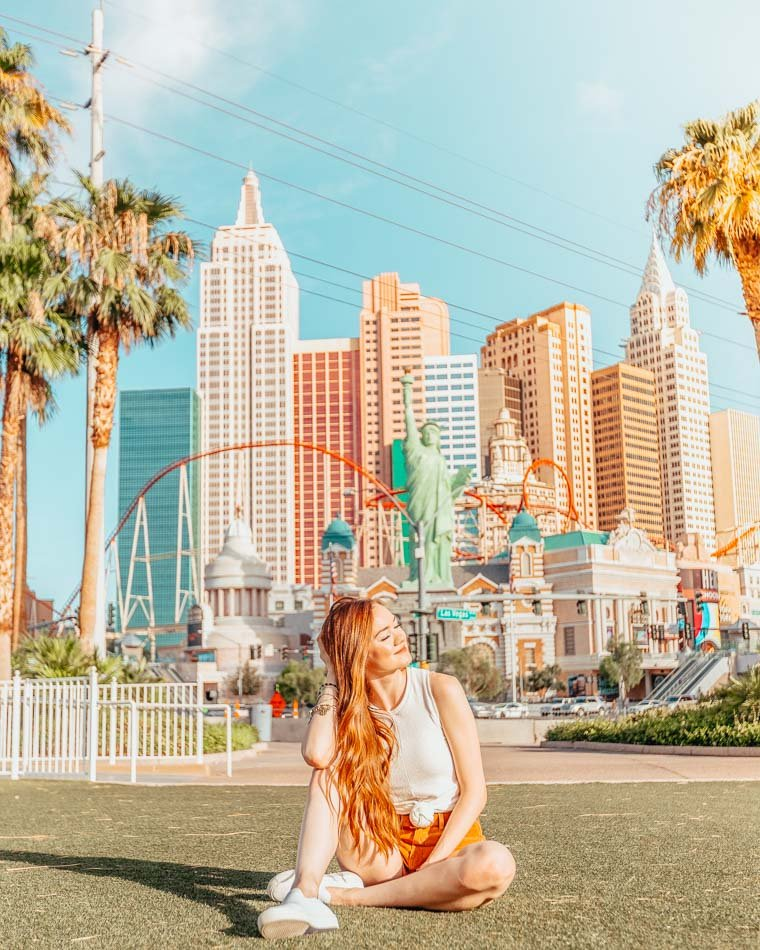 """Girl sitting infant of the entrance to """"New York New York"""" in Las Vegas."""