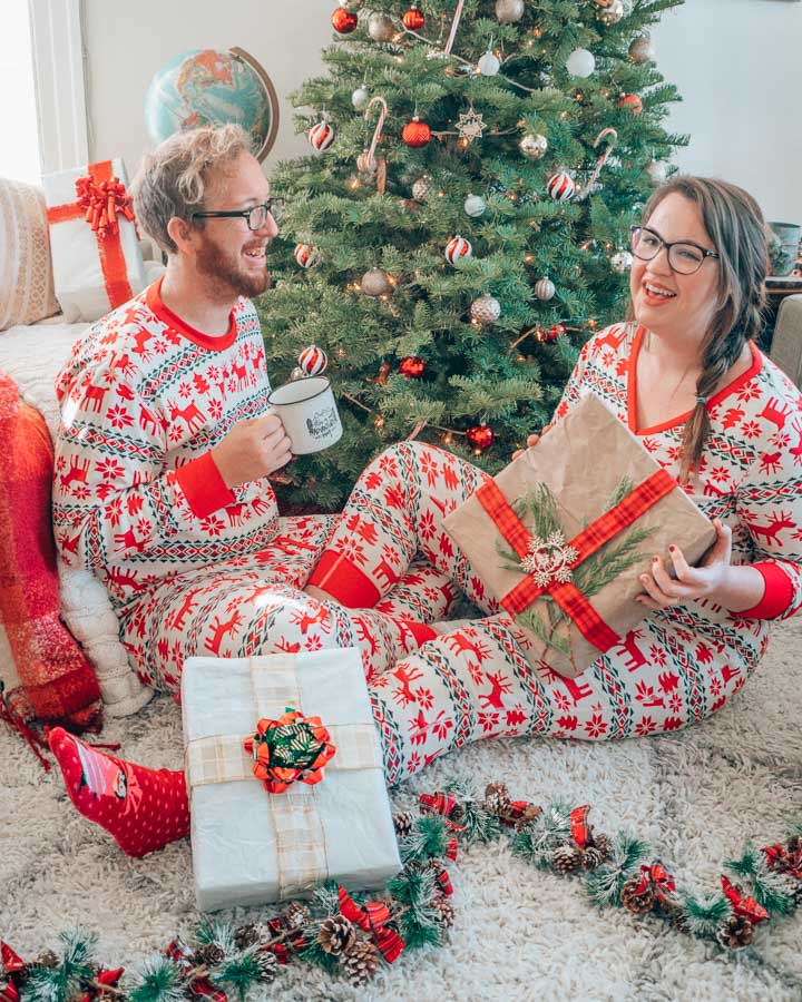 Lia and Jeremy in matching Christmas PJs in front of a Christmas tree.