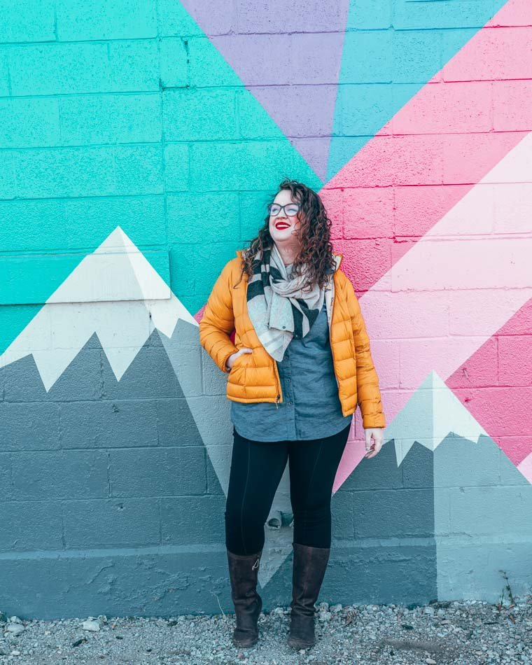 Lia in a down jacket in front of a mountainy street mural in Salt Lake City, Utah.