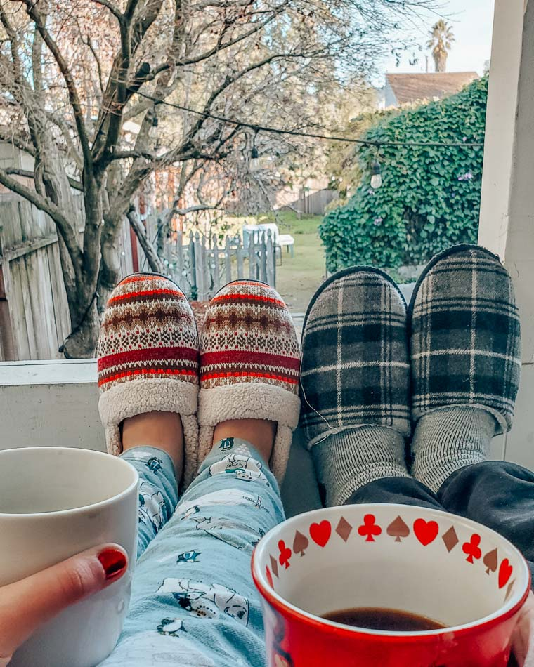 Two pairs of slippers and two coffee mugs overlooking a wintery backyard.