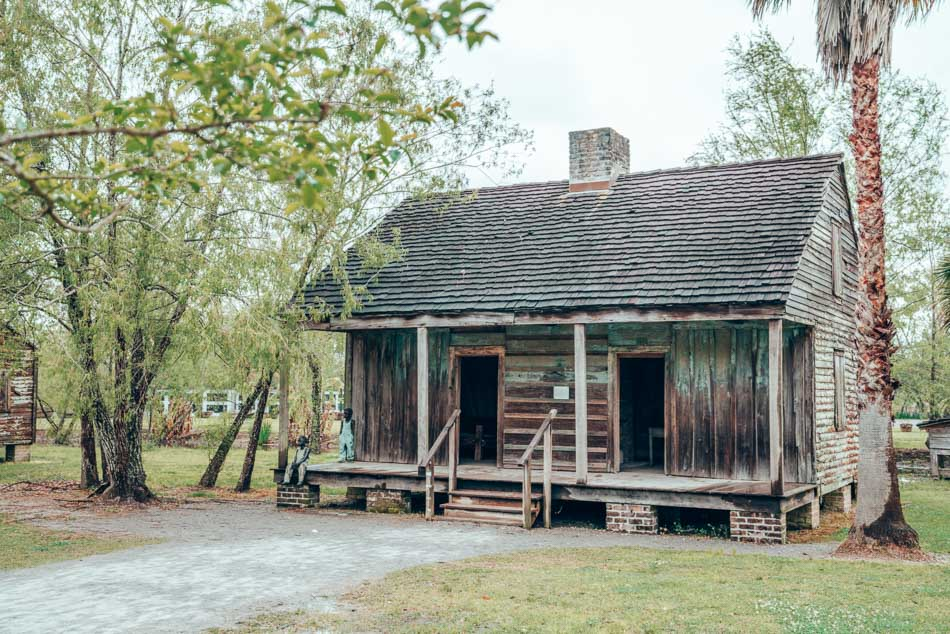 A plantation home at the Whitney Plantation, with statues of the children who lived there.