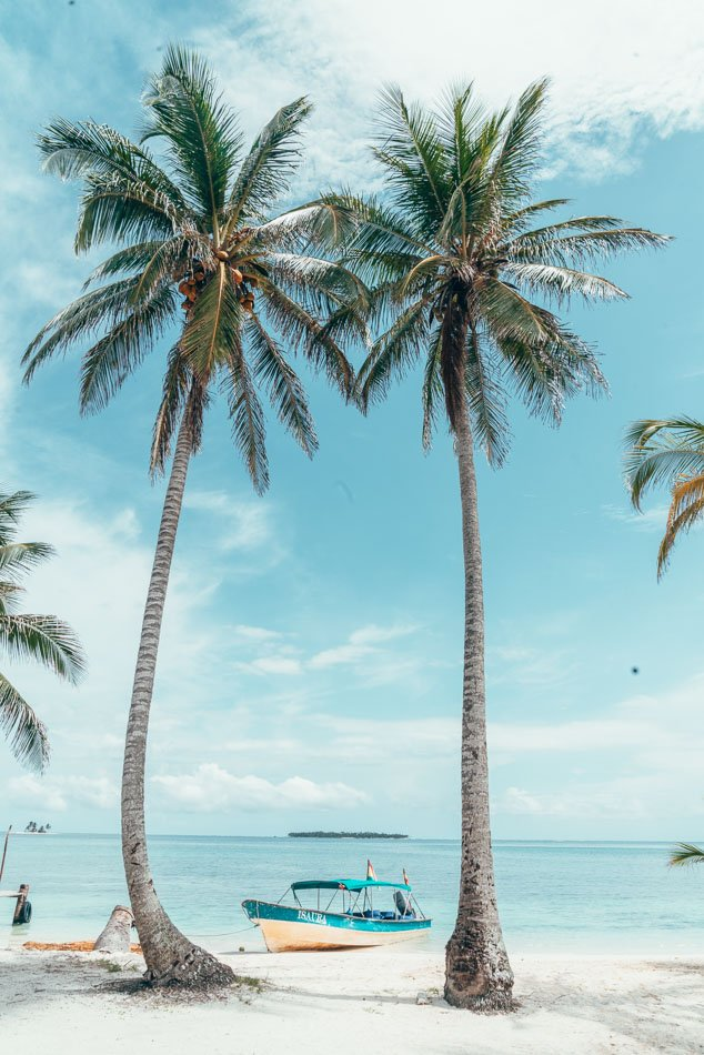 Palm trees and a boat on the Caribbean Sea in the San Blas Islands, Panama.