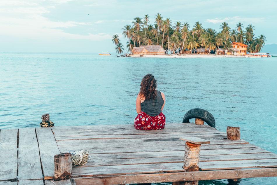 Girl sitting on dock looking at tiny island in the San Blas Islands aka Guna Yala, Panama.