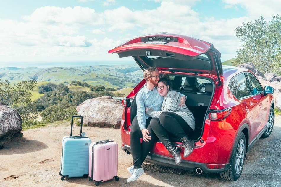 Couple in Red Car with Suitcases California Highway One Road Trip