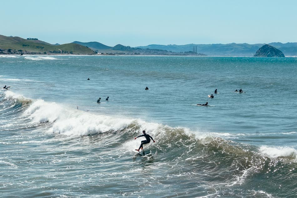 Surfers catching waves with Morro Rock in the background.