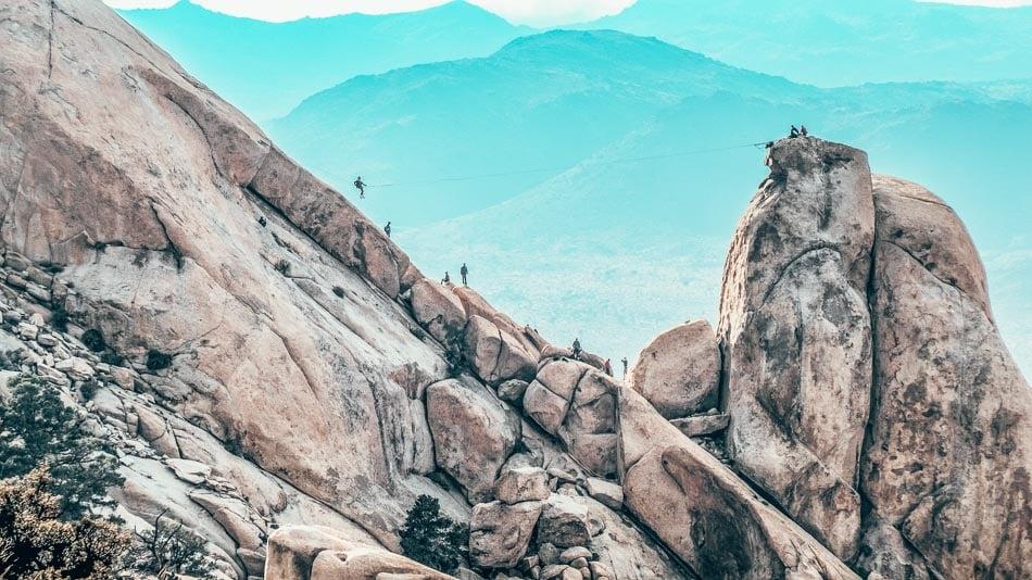 Rock climbers clamboring over the rocks in Joshua Tree national park along the Ryan Mountain trail!