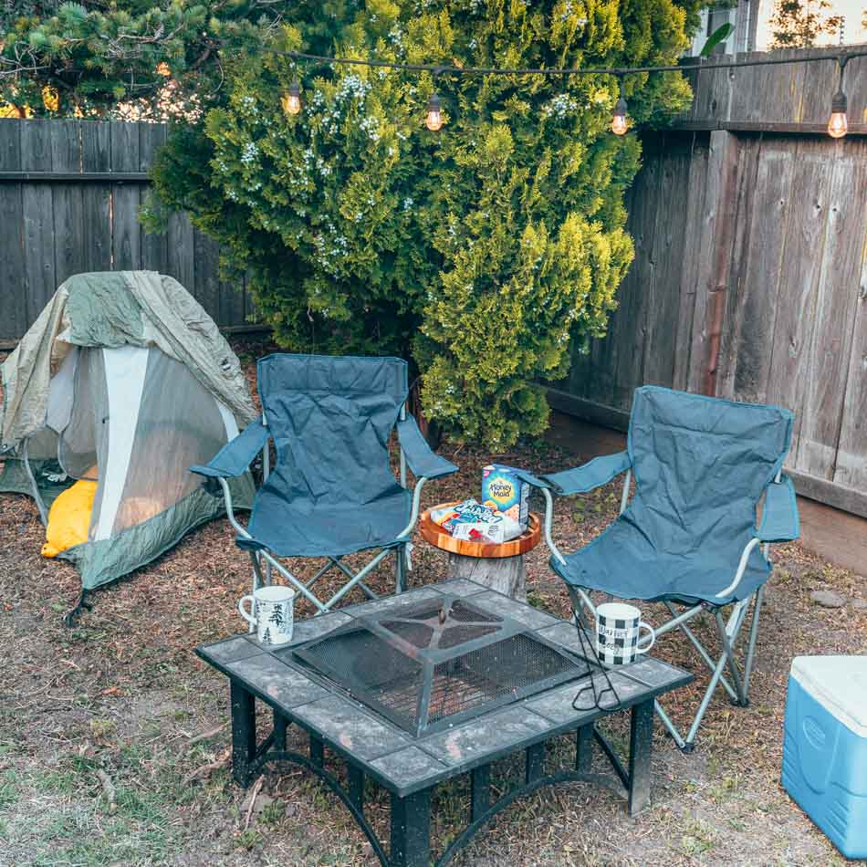Backyard camping set-up with firepit, camp chairs, tent, string lights, and s'mores supplies.