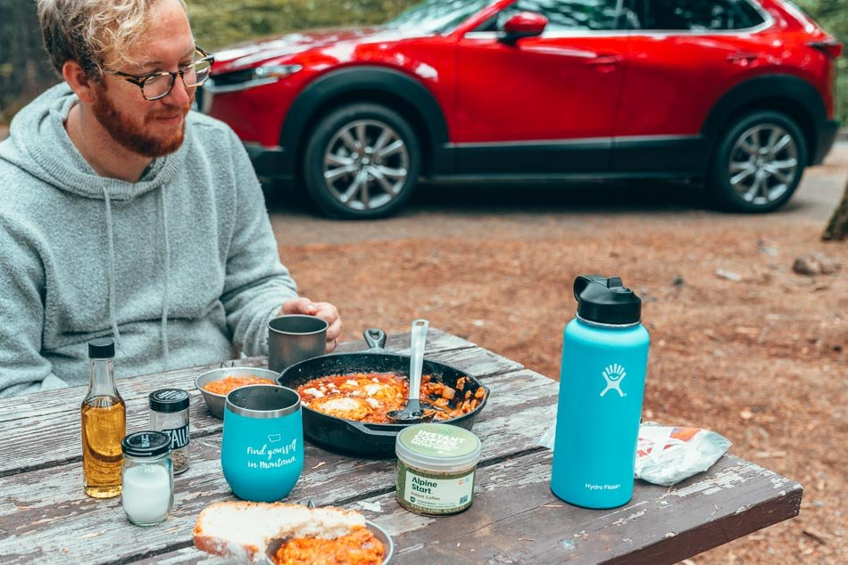 Shakshuka in a cast iron skillet while camping in Northern California in front of a red Mazda CX-30.