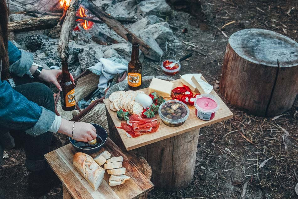 Charcuterie board by a campfire! Packing your camp kitchen is one of the most important things to go on your camping checklist.