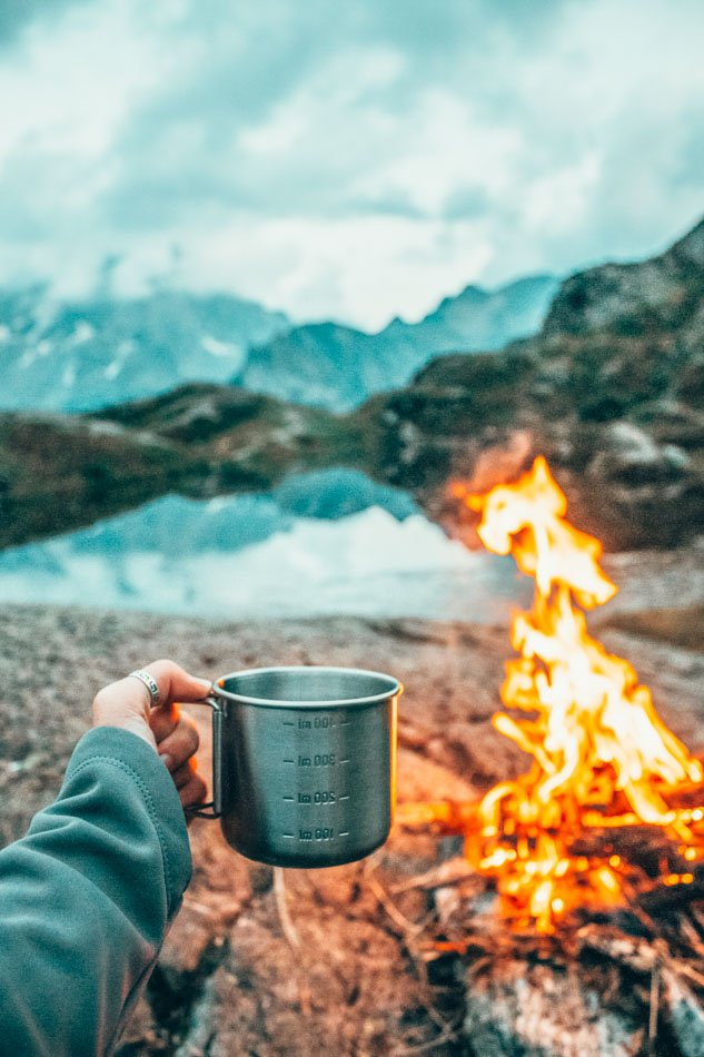 Coffee by the fire with a view of mountains and a lake.