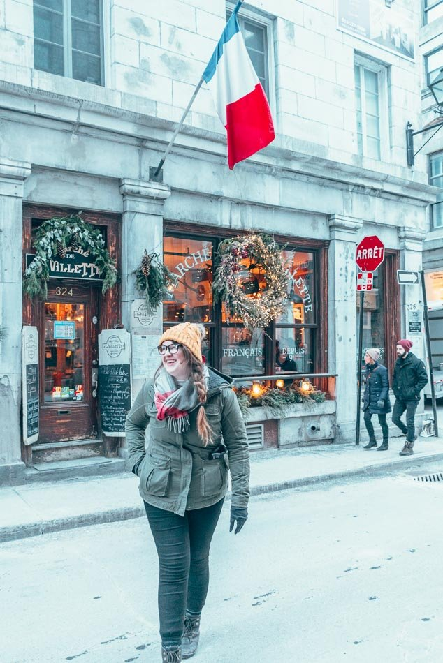 Girl walking in Old Town Montreal in the winter, in front of a French flag.