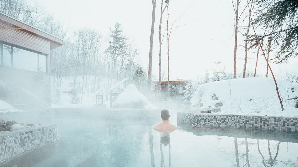 Man inside hot tub at a Nordic Spa in Canada.