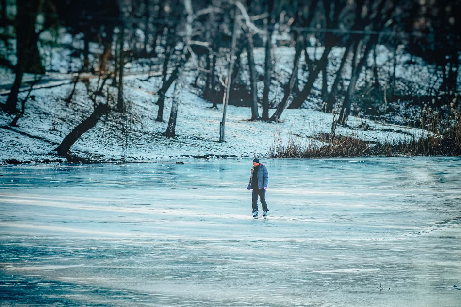Man ice skating on the alpine lake in Jackson Hole, WY.