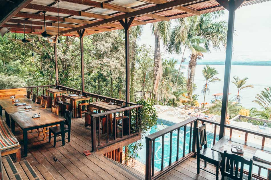 Bambuda Hostel in Bocas del Toro, Panama overlooking a pool, palm trees, and the Caribbean sea.