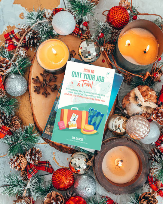How to Quit Your Job & Travel book surrounded by Christmas decorations and candles. Give the gift of long-term travel!