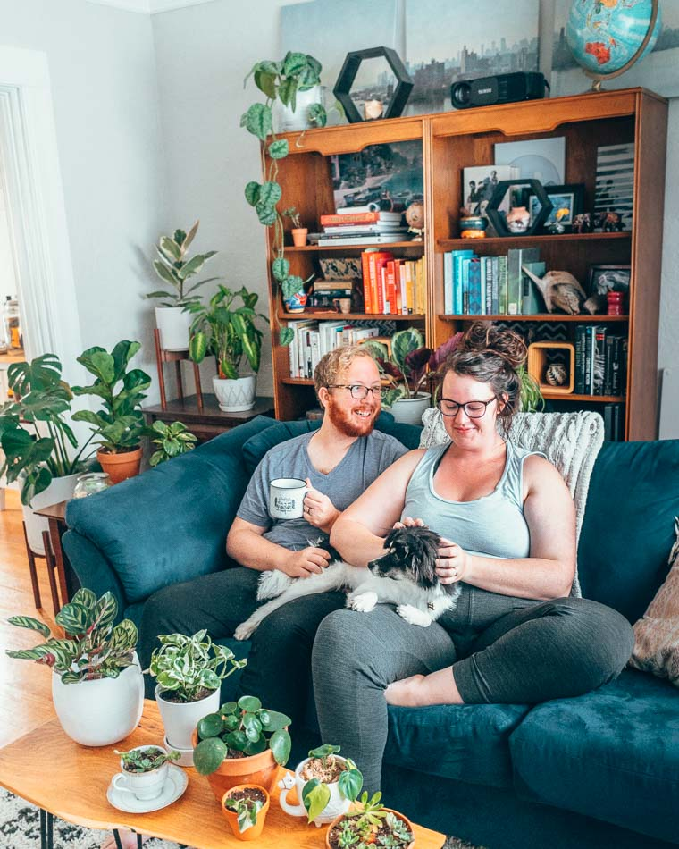 A couple and their dog on a blue couch, surrounded by plants and books.