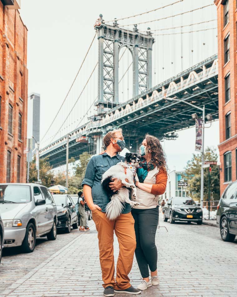 Couple and Dog under the Brooklyn Bridge in New York City wearing masks