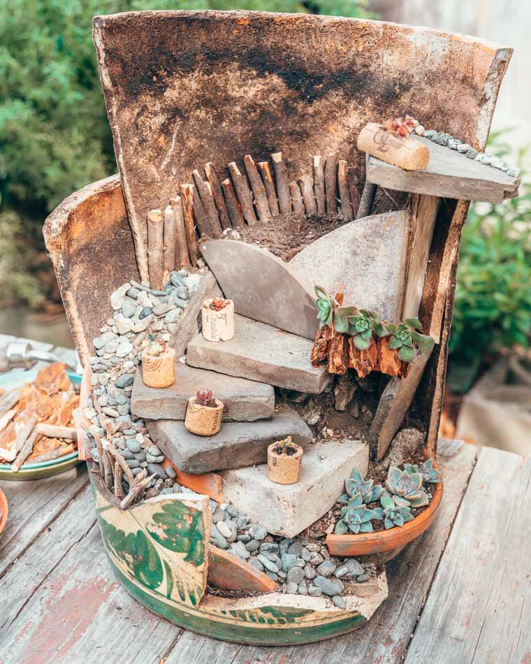 Fairy garden made from a broken pot, with tiny succulent planters in wine corks