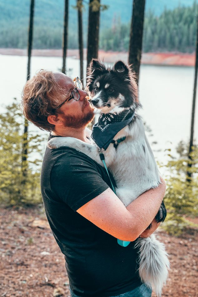 Jeremy holding Mulan in the Trinity Alps Wilderness, in front of a lake.