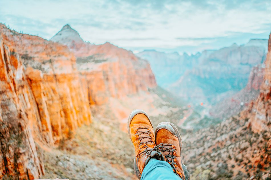 Close up of man wearing mountain boots and landscape of mountains in Zion National Park.