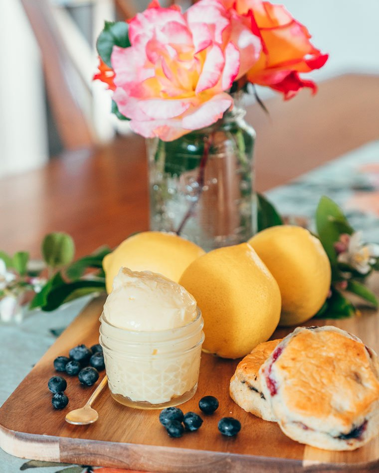 Lemon curd with scones and roses in the background