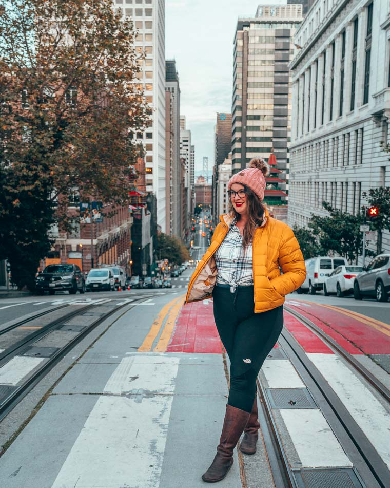 Girl in yellow jacket in San Francisco, California crossing the street, with a view of the Bay Bridge in the background.