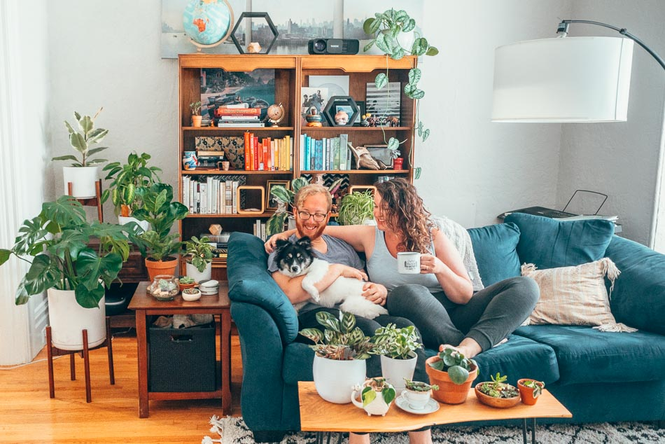 Couple and dog on a blue couch, surrounded by plants in front of a colorful bookshelf.