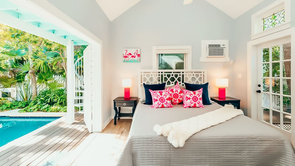 Colorful bedroom in Key West, Florida decorated with pink flamingo decor and a pool steps away from the bed.