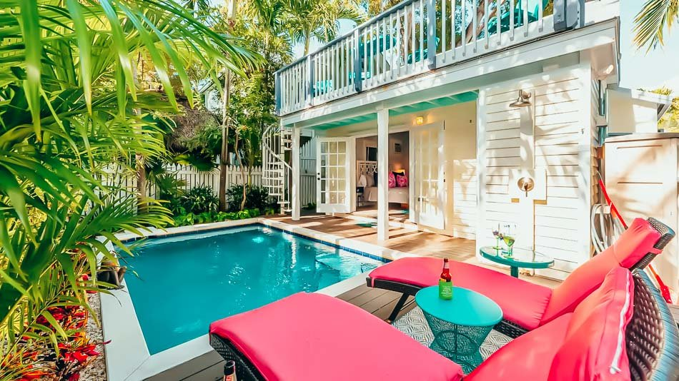 Private pool surrounded by lush tropical foliage and pink chairs in Key West, Florida.