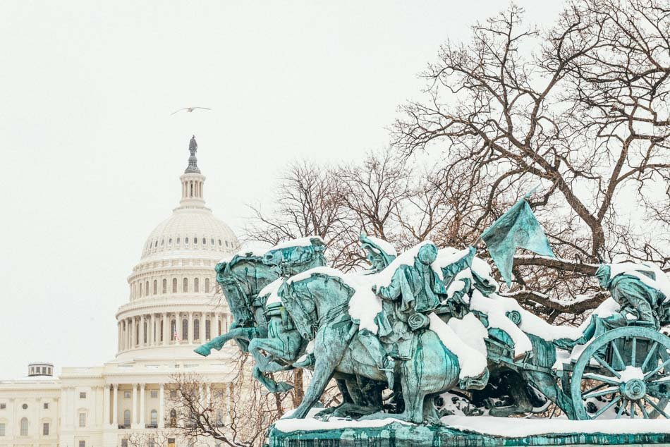 The US Capitol in the daytime during snowfall with a view of the Grant Memorial.