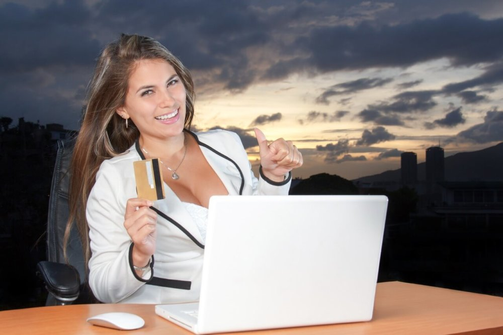 Girl in suit holding a credit card and making a thumbs up sign while looking at a computer.