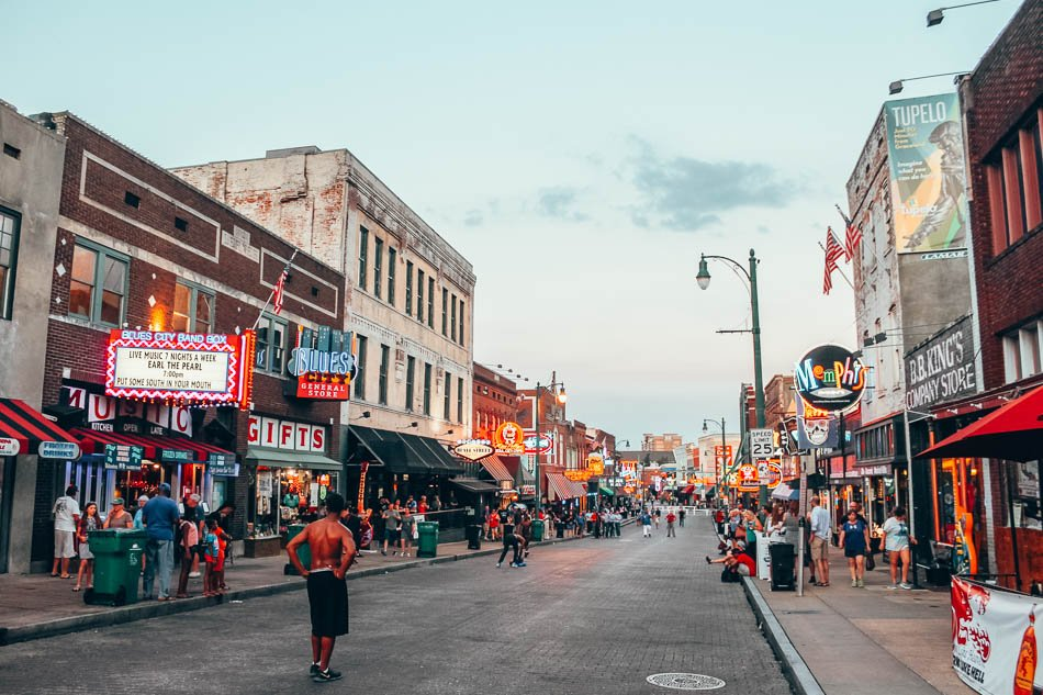 Beale Street at Twilight in Memphis, Tennessee, with street performers and neon signs.