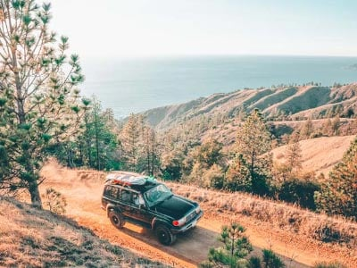 Car drives on a cliff overlooking rolling hills and the sea on the Pacific Coast Highway in California.