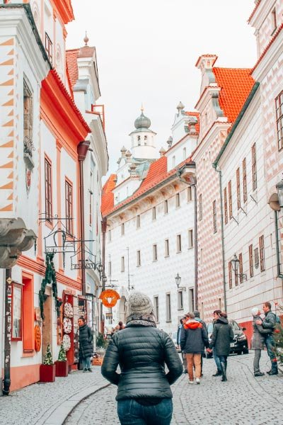 Girl exploring cobblestone city streets surrounded by pink buildings in Cesky Krumlov, Czech Republic.