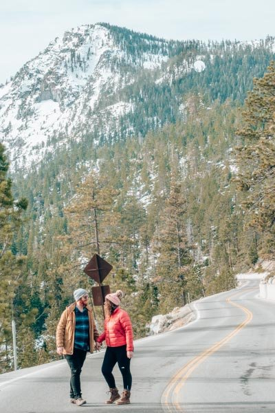 Couple on a road in front of snowy mountains covered with pine trees in Lake Tahoe, California.