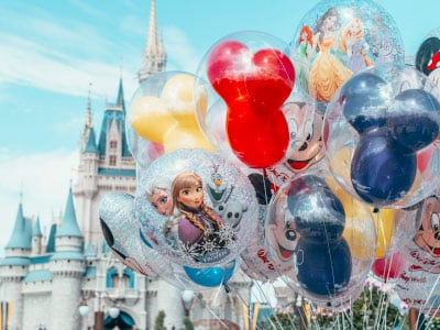 Brightly colored balloons featuring Disney characters in front of a castle on a sunny day in Disney World, Florida