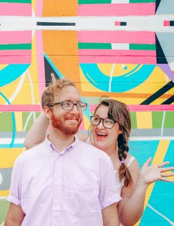 Couple being silly against a brightly colored graffiti background.