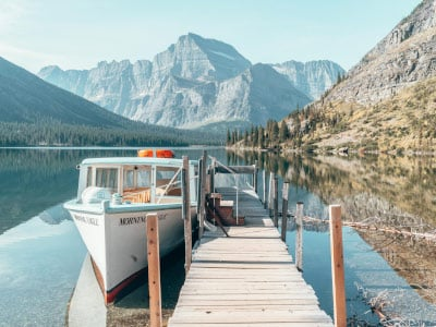 Boat moored to a dock on a mirrored lake with a mountain looming in the background in Glacier National Park, Montana