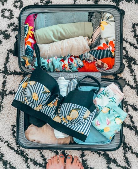 Suitcase packed with beach supplies, a lemon-printed bikini, and heart-shaped sunglasses on a black and white patterned carpet.