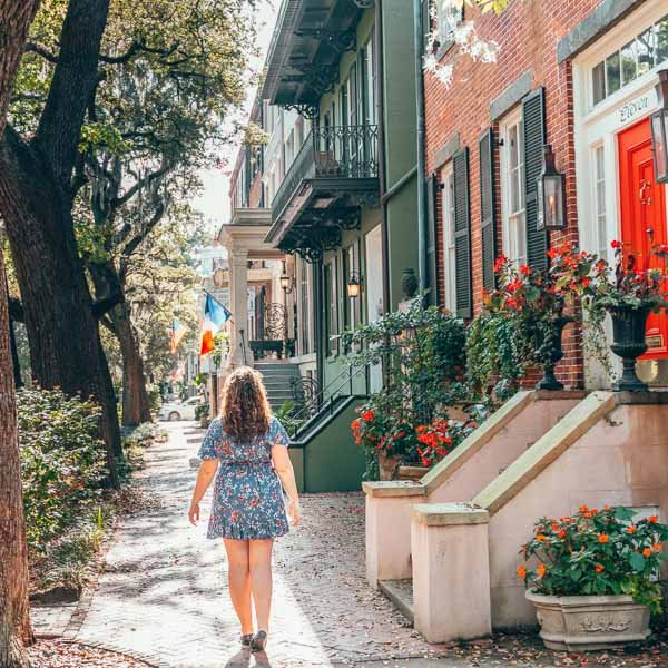 Girl with curly hair in a blue flowered dress exploring the cobblestone streets of Savannah, Georgia in the spring time next to red flowers and a bright red door.