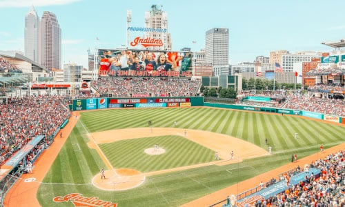 Crowds pack the stadium of a baseball field, with a sign showing the Indians are playing.